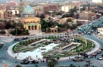 A long shot of Firdos Square during the statue toppling process. A small knot of onlookers can be seen surrounding the statue at the far end of the area; most of the square is empty. Three US tanks can be seen stationed around the square.