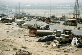Demolished and disabled vehicles litter the 'Highway of Death' in the hours after Iraqi forces were slaughtered by US strikes.