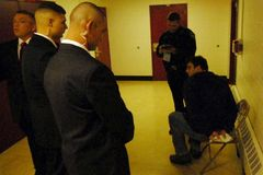 Several of Joe Miller's private security guards stand over a handcuffed Tony Hopfinger, whom they detained during a political event.