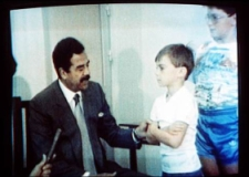 Saddam Hussein inquires about the health of young British hostage Stuart Lockwood, a scene broadcast on Iraqi television and shown worldwide.