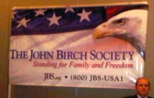 The John Birch Society booth displays a banner at the 'Freedom Rally' before the debate.