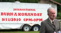 A photo of Terry Jones standing in front of a sign announcing 'International Burn a Koran Day,' originally planned for September 11, 2010.