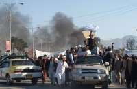 Smoke billows from the burning UN mission in Mazar-i-Sharif, as protesters take to the streets.