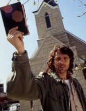 David Koresh holds up a Bible while standing in front of a church.