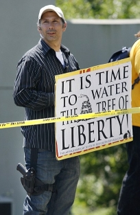 Protester William Kostric, bearing his sign and wearing a gun strapped to his leg.