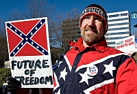 A League of the South member at a 2008 political rally. This member is wearing a button supporting the candidacy of Ron Paul (R-TX). The sign behind the supporter calls the NAACP a &#8220;racist&#8221; organization.