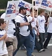 Supporters of Joe Miller march while carrying assault weapons.
