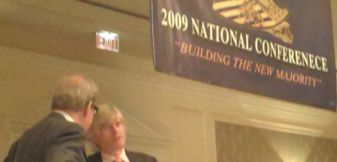 English-only advocates Pat Buchanan and white nationalist Peter Brimelow standing under misspelled banner.