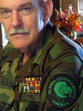 Norm Olson. Olson is wearing an 'Alaska Citizens' Militia' shoulder patch as part of his pseudo-military garb.