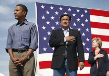 Presidential candidates Barack Obama (left), Tom Harkin, and Hillary Clinton stand for the singing of the National Anthem.