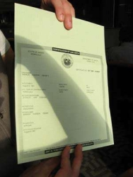 A photograph of the actual Hawaiian birth certificate of Barack Obama, being held by FactCheck (.org) writer Joe Miller.