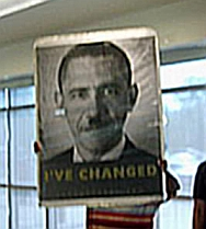 An anti-reform protester displays a large sign depicting President Obama as Adolf Hitler.