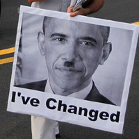 An anti-health care reform protester carries a poster depicting President Obama as Adolf Hitler.