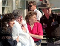 A bloodied survivor is helped from the Murrah bomb site.
