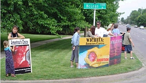 Anti-abortion protesters gather on a street corner in Wichita.