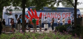 Patients First bus featuring the &#8220;Hands Off Our Health Care&#8221; slogan and bloody handprint logo.