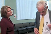 Ron Paul (r) removes his mic as CNN reporter Gloria Borger looks on.