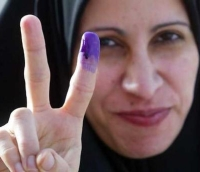 An Iraqi voter displays her purple finger for a reporter's camera.