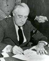 President Roosevelt signs the US declaration of war with Japan.
