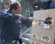 Montana Governor Brian Schweitzer uses a branding iron to &#8216;veto&#8217; a number of tea party-sponsored bills passed by the Montana legislature.
