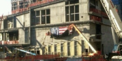A crane begins removing an American flag from the 'Ground Zero' site of the former World Trade Center.