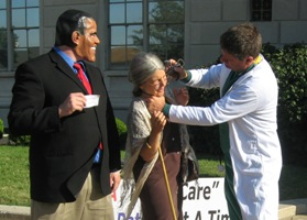 Health reform organizer Randall Terry pretends to stab an elderly lady in the neck as part of an anti-reform protest. A fellow protester wearing a Barack Obama mask looks on.