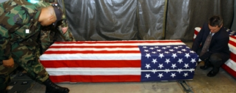 A military photo of a flag-draped casket.