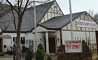 Part of the Westboro Baptist Church as it appears in recent years. The URL &#8220;godhatesamerica.com&#8221; is written on a banner hanging in front of the church.