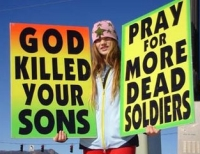Signs held by a WBC picketer at the funeral of a fallen soldier.