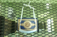 A Koran kept for detainees' use at Guantanamo. The surgical mask is provided to keep the Koran off the floor, and the guards from touching the book.