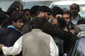 Iftikhar Chaudhry being arrested by secret agents. An agent is holding Chaudhry&#8217;s hair as he is being pushed into a car. 