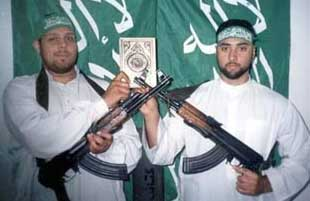 Asif Hanif (left) and Omar Sharif (right) holding AK-47 rifles and a Koran. Apparently this is from a video filmed on February 8, 2003, in the Gaza Strip.