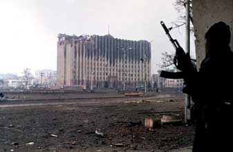 A Chechen rebel looks at the government palace in Grozny, Chechnya, in January 1995.