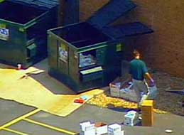 An FBI agent checking a dumpster near Steven Hatfill's apartment.